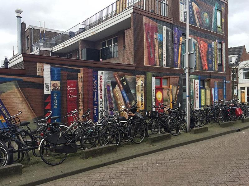 giant 3d bookshelf street art by jan is de man and deef feed 5 Dutch Artists Paint Giant 3D Bookshelf of Neighborhoods Favorite Books